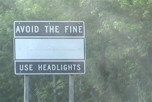 Avoid the fine: use headlights (black sign, white text)