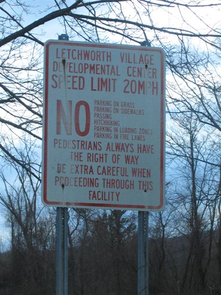 Letchworth Village Developmental Center; Speed Limit 20 mph; NO: Parking on grass, parking on sidewalks, passing, hitchhiking, parking in loading zones, parking in fire lanes; Pedestrians always have the right of way; Be extra careful when proceeding through this facility